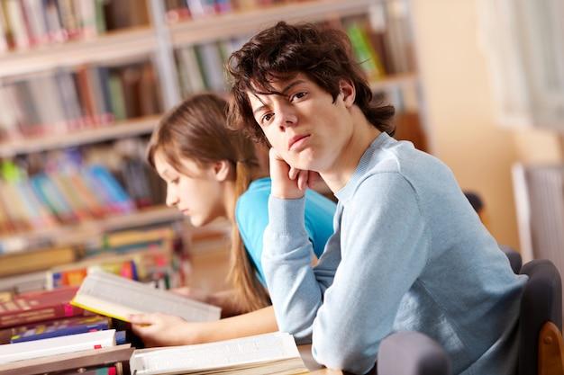 Ernster jugendlicher in der bibliothek
