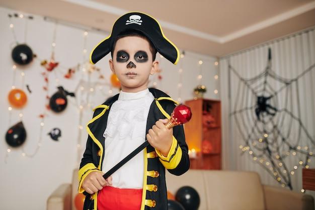 Ernster jugendlicher junge im piratenkostüm posiert mit zepter auf halloween-party