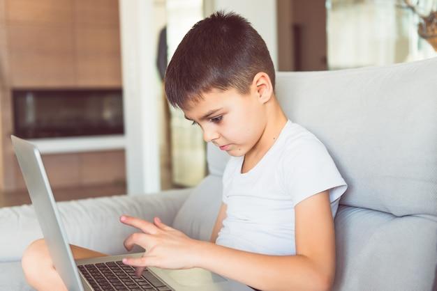 Ernster junge, der auf sofa sitzt, hat internetverbindung, computerspiele spielen, online-schulung. kindheit, internet, geräte, bildung, computerspielekonzept. getönt