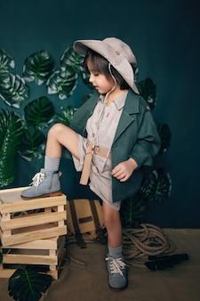 Ernster junge kinderreisender in einem hut stehen auf holzkisten in einem studio auf einem grünen hintergrund