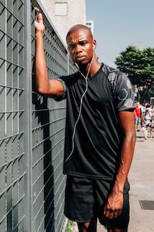 Ernster junger afrikanischer männlicher athlet mit kopfhörer in seinen ohren, die vor grauem tor stehen