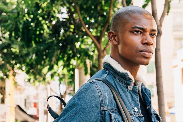 Ernster junger afrikanischer mann mit rucksack auf seiner schulter, die weg schaut