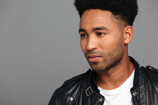 Ernster junger afroamerikanischer kerl mit dem stilvollen haarschnitt, der beiseite schaut