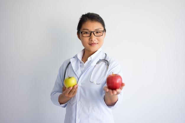 Ernster junger asiatischer weiblicher doktor, der roten apfel anbietet. gesundes ernährungskonzept.