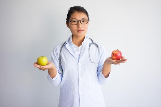 Ernster junger asiatischer weiblicher doktor, der roten und gelben apfel anhält.