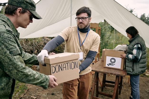 Ernster junger bärtiger sozialarbeiter mit abzeichen, der im freien eine spendenbox an einen soldaten weitergibt
