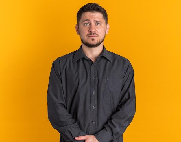 Ernster junger blonder gutaussehender mann, der nach vorn schaut, isoliert auf orange wand