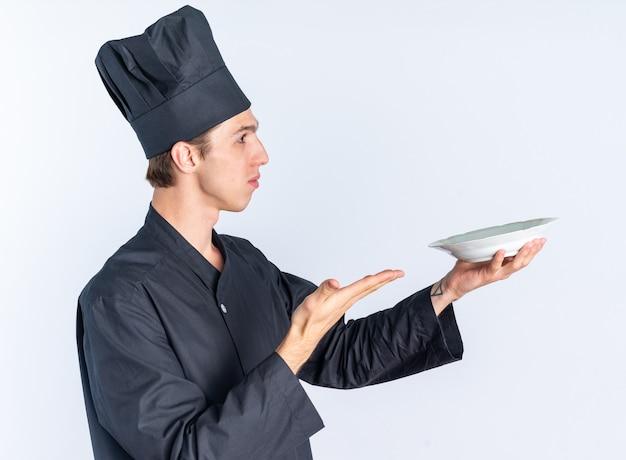Ernster junger blonder männlicher koch in kochuniform und mütze, der in der profilansicht steht, sich ausstreckt und mit der hand auf den teller zeigt, der auf die seite isoliert auf der weißen wand blickt