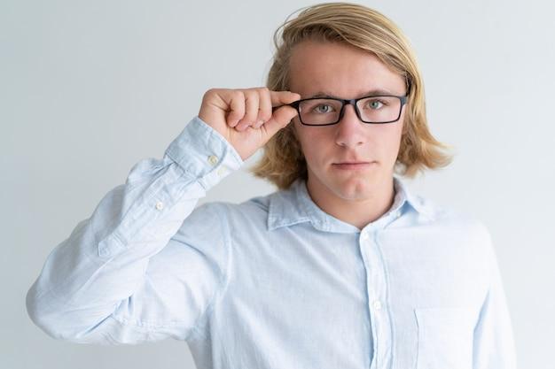 Ernster junger blonder mann, der gläser justiert