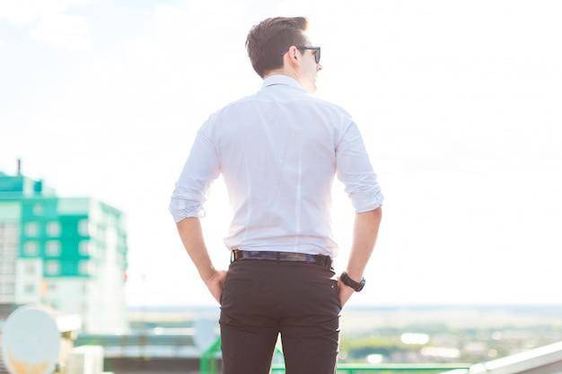 Ernster junger busunessman im weißen hemd, in der bindung und in der sonnenbrille stehen auf dem dach