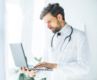 Ernster junger Doktor, der Laptop durchstöbert