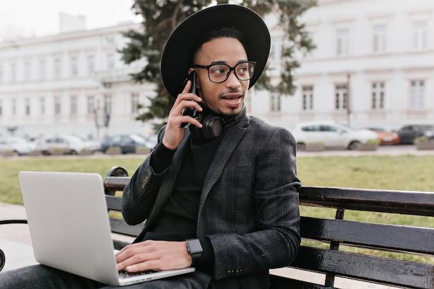 Ernster junger geschäftsmann, der am telefon spricht, während er mit computer im park arbeitet. foto im freien des beschäftigten afrikanischen kerls unter verwendung des laptops im quadrat.