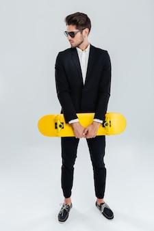 Ernster junger geschäftsmann, der gelbes skateboard über grauer wand hält