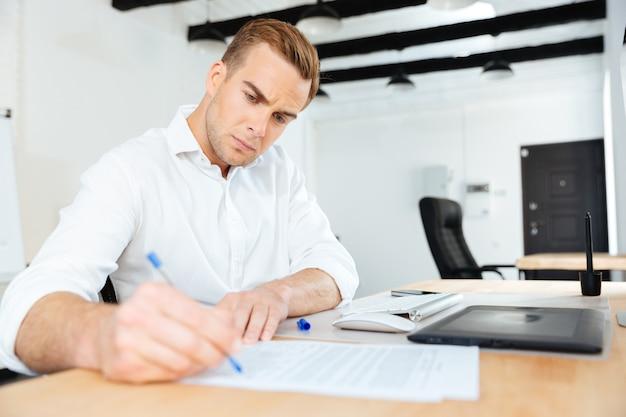 Ernster junger geschäftsmann, der im büro sitzt und schreibt