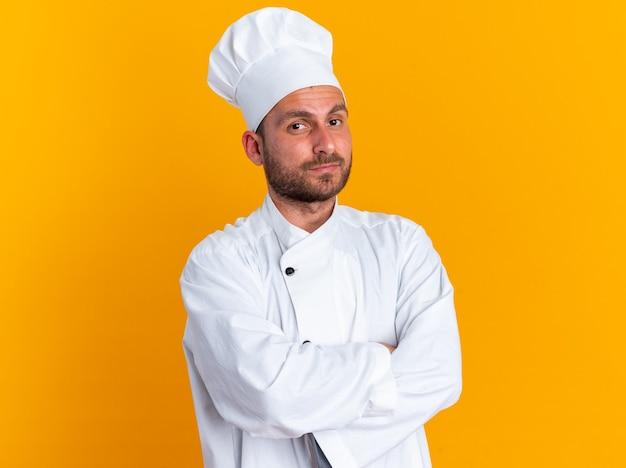 Ernster junger kaukasischer männlicher koch in kochuniform und mütze, der mit geschlossener haltung in die kamera schaut, die auf orangefarbener wand isoliert ist?