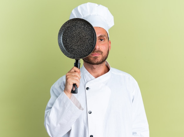 Ernster junger kaukasischer männlicher koch in kochuniform und mütze, die die hälfte des gesichts mit bratpfanne bedeckt, die von hinten in die kamera schaut, isoliert auf olivgrüner wand