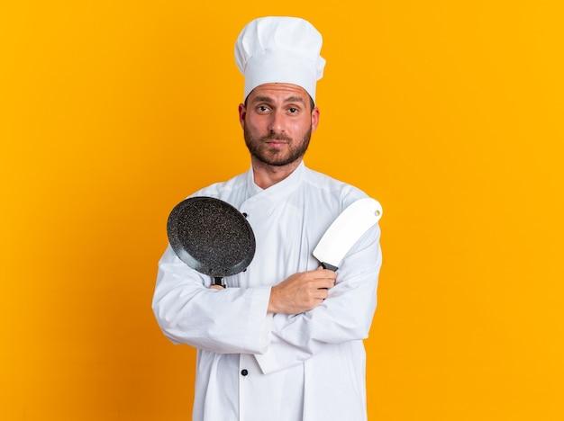 Ernster junger kaukasischer männlicher koch in kochuniform und mütze stehend mit geschlossener haltung mit hackmesser und bratpfanne mit blick auf die kamera isoliert auf oranger wand mit kopierraum