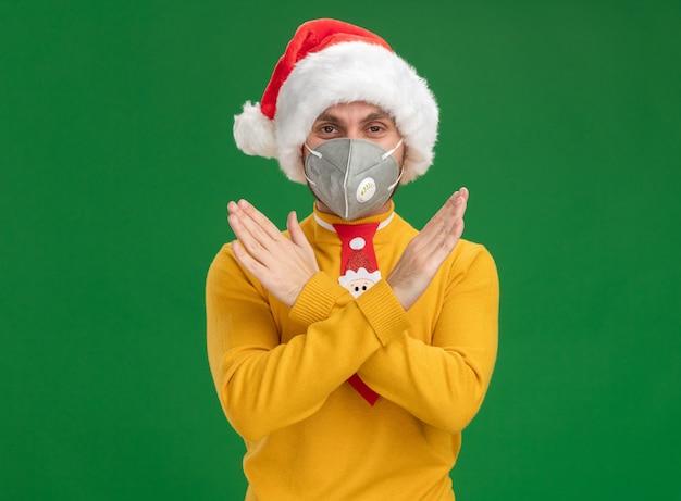 Ernster junger kaukasischer mann mit weihnachtsmütze und krawatte mit schutzmaske, der keine geste isoliert auf grüner wand mit kopierraum sieht