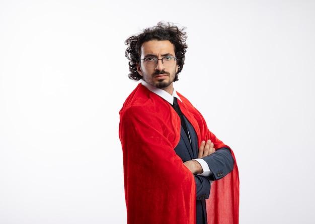 Ernster junger kaukasischer superheldenmann in optischer brille, der anzug mit rotem mantel trägt, steht seitlich mit verschränkten armen