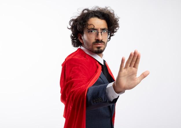 Ernster junger kaukasischer superheldenmann in optischer brille, der anzug mit rotem mantel trägt, steht seitlich und gestikuliert stopphandzeichen
