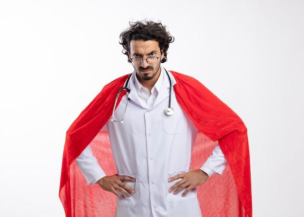 Ernster junger kaukasischer superheldenmann in optischer brille, der eine arztuniform mit rotem mantel trägt und mit stethoskop um den hals die hände auf die taille legt