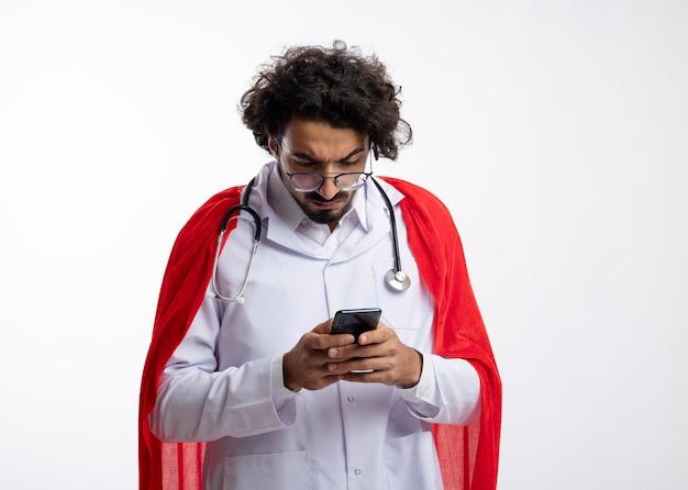 Ernster junger kaukasischer superheldenmann in optischer brille, der eine arztuniform mit rotem umhang trägt und mit stethoskop um den hals hält und auf das telefon schaut