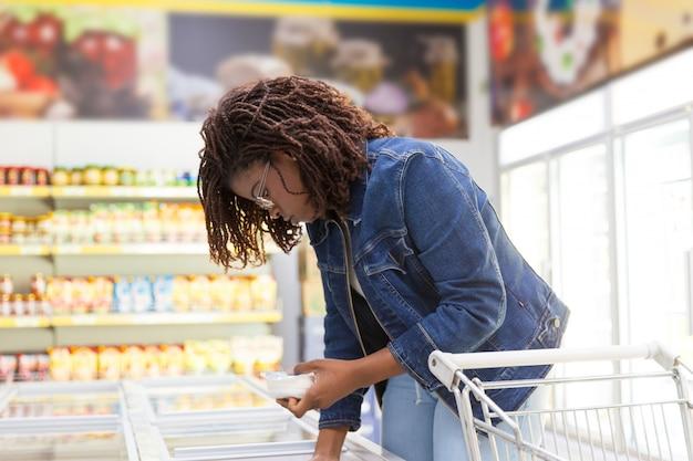 Ernster junger kunde, der produkt vom gefrierschrank nimmt
