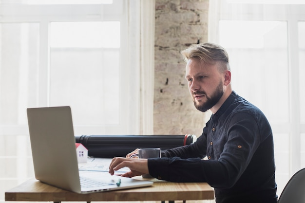 Ernster junger mann, der an laptop im büro arbeitet