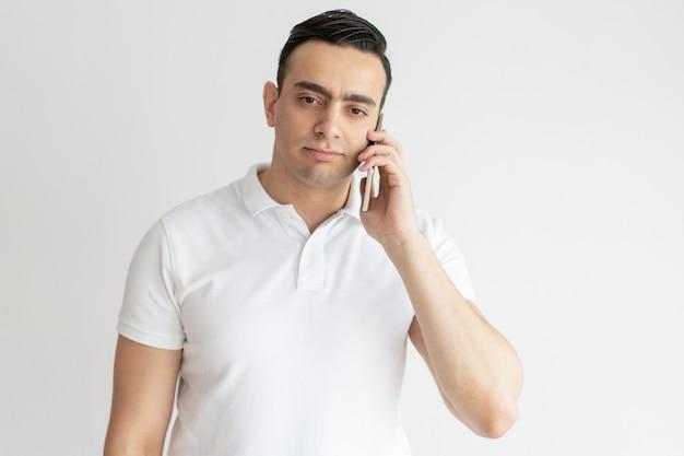 Ernster junger mann, der auf smartphone spricht und kamera betrachtet