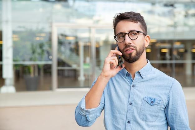 Ernster junger mann, der durch smartphone spricht