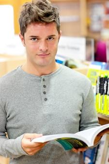 Ernster junger mann, der ein buch liest