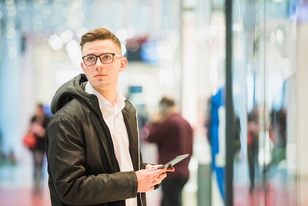 Ernster junger mann, der in der hand die digitale tablette weg schaut hält