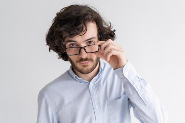 Ernster junger mann, der kamera über gläsern betrachtet