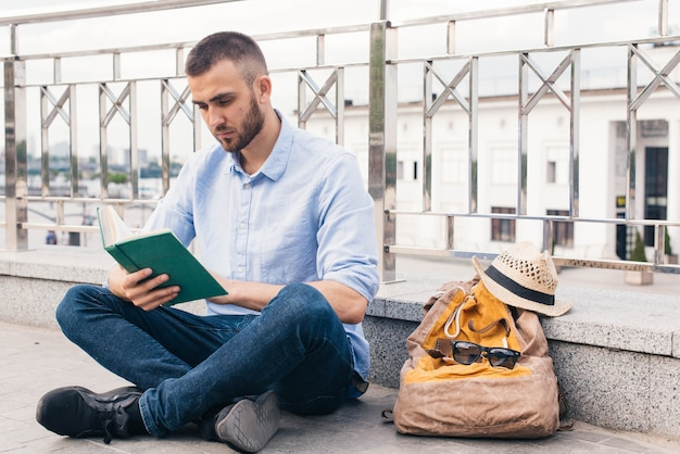 Ernster junger mann, der nahe geländer am freien und am lesebuch sitzt