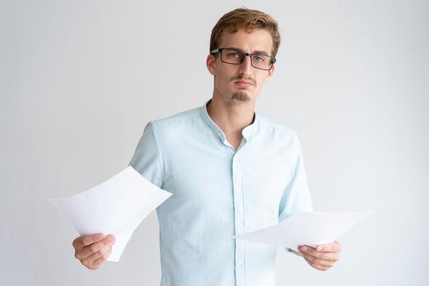 Ernster junger mann, der papierblätter hält und kamera betrachtet