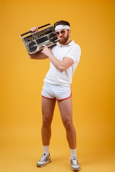 Ernster junger mann, der sonnenbrille hält, die tonbandgerät hält
