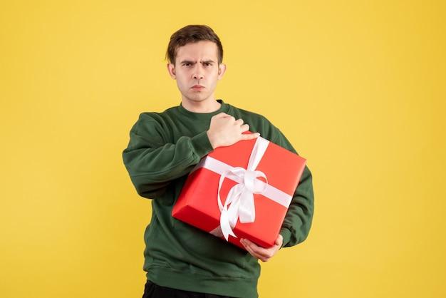 Ernster junger mann der vorderansicht mit grünem pullover, der auf gelb steht