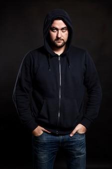 Ernster junger mann in einem pullover mit einer kapuze auf einem schwarzen hintergrund. banditentum und verbrechen. vertikal.