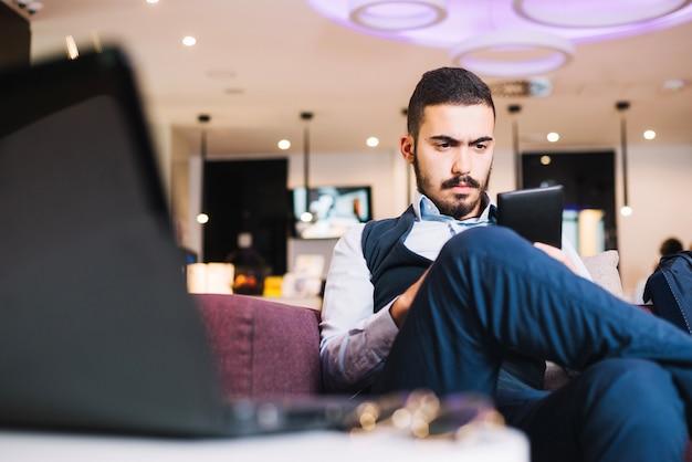 Ernster junger mann konzentrierte sich auf telefon