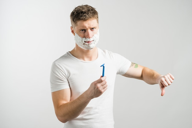 Ernster junger mann mit dem rasierschaum auf seinem gesicht, das in der hand das blaue rasiermesser zeigt daumen unten gegen grauen hintergrund hält