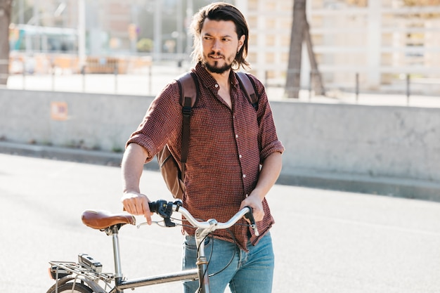 Ernster junger mann mit seinem rucksack gehend mit fahrrad
