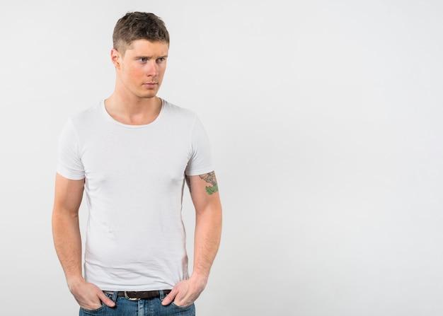 Ernster junger mann mit seinen zwei händen in der tasche, die weg schaut
