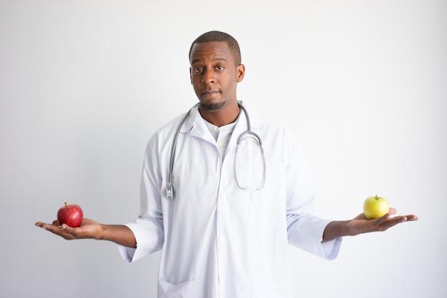 Ernster junger schwarzer männlicher doktor, der die grünen und roten äpfel hält.