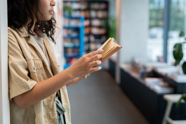 Ernster junger student in freizeitkleidung, der buch liest
