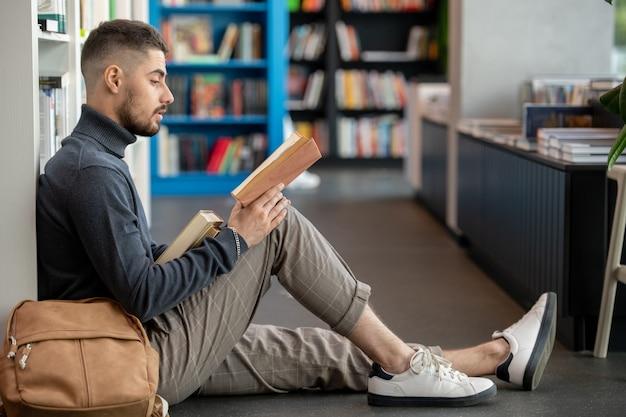 Ernster junger student in freizeitkleidung, der gegen bücherregale sitzt