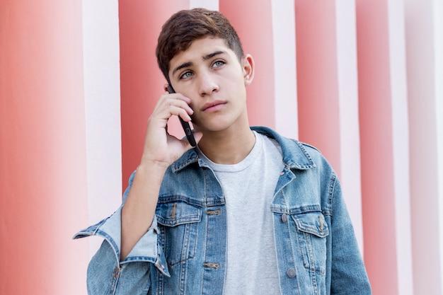 Ernster junger teenager, der auf mobiltelefon an draußen spricht