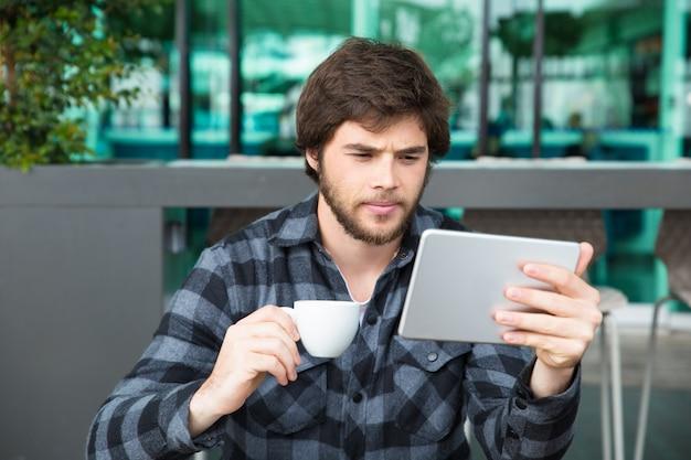 Ernster junger unternehmer, der oben wirtschaftsnachrichten überprüft