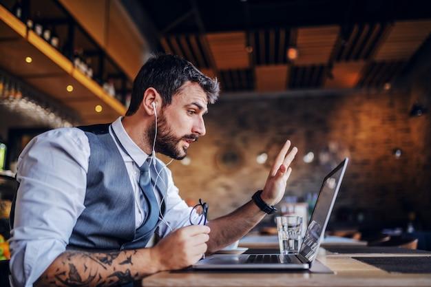 Ernster kaukasischer hübscher bärtiger geschäftsmann im anzug, der videoanruf über laptop beim sitzen im café hat.