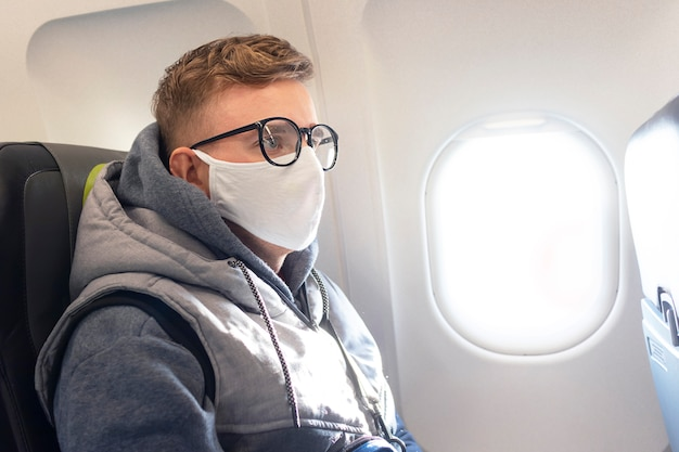 Ernster kerl, junger mann im flugzeug, flugzeug in brille und sterile medizinische schutzmaske auf seinem gesicht unterwegs. coronavirus, virus, airline-konzept. pandemie covid-19. sicherheit im öffentlichen verkehr