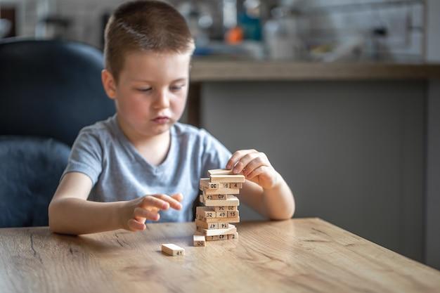 Ernster kleiner junge, der brettspiel mit hölzernem turm spielt.